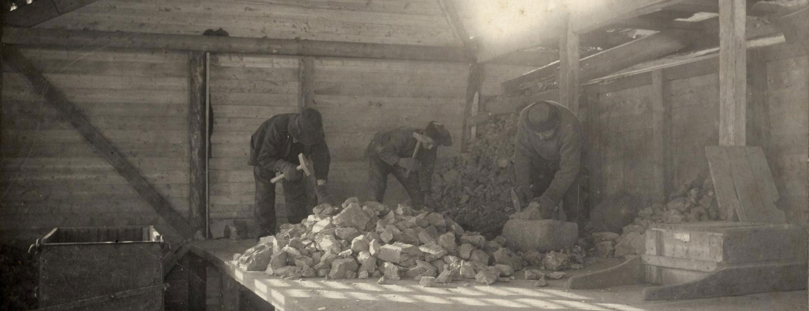 Bildet viser tre menn som hugger stein fra gruven.
