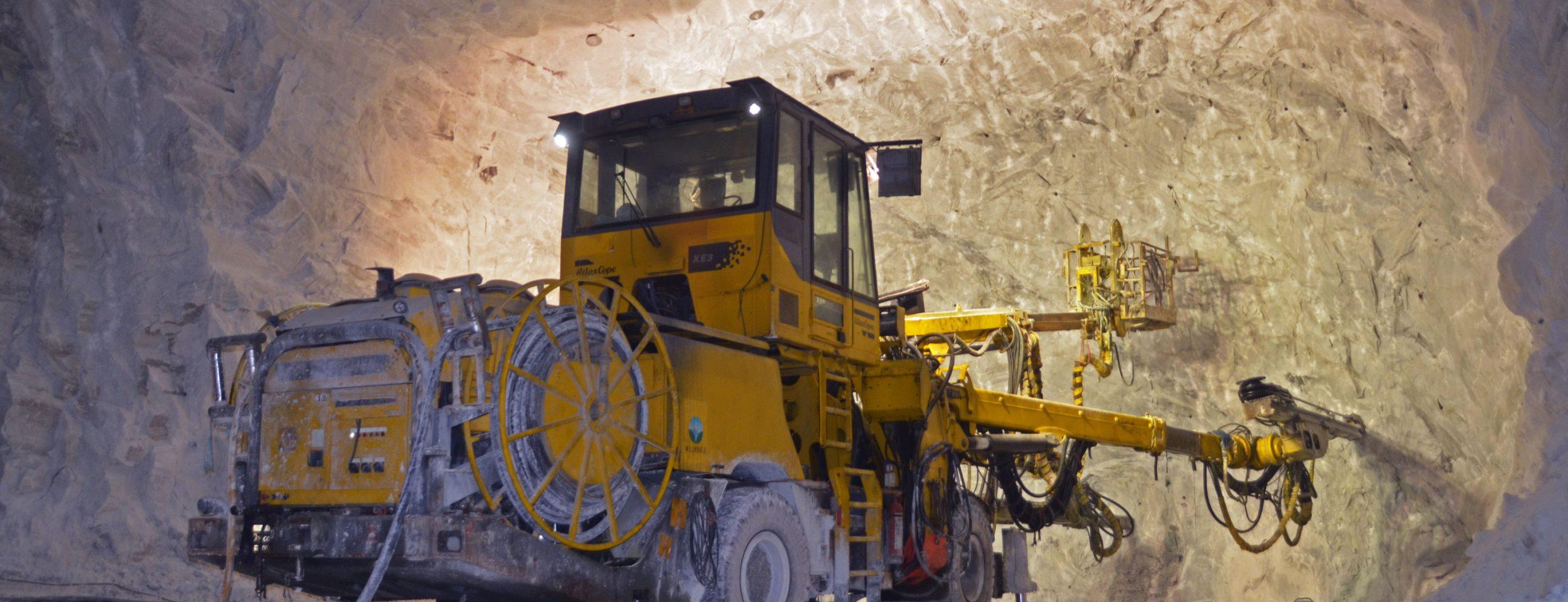 Bildet viser en stor borremaskin inni en gruve, som borrer seg innover i fjellet.