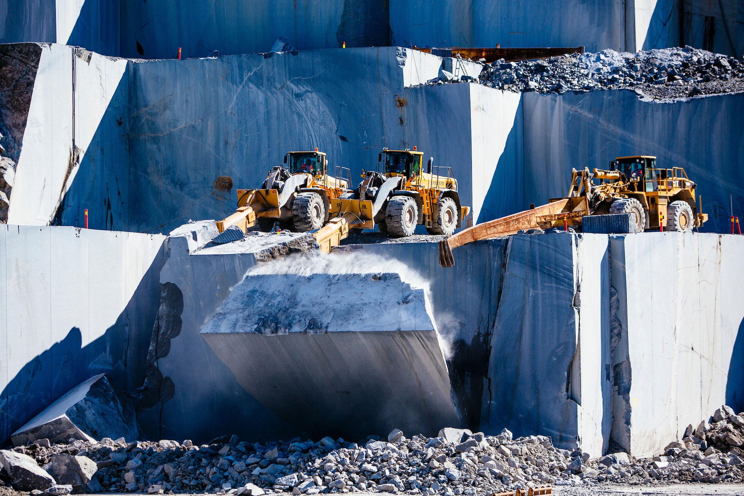 Bildet viser to gravemaskiner under arbeid i steinbruddet.