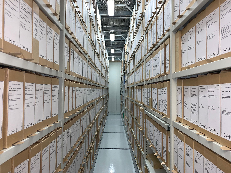 Bildet viser høye og lange magasiner fyllt med gamle arkiver.