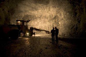 Bildet viser to menn og en borremaskin i en stor hul gruve.