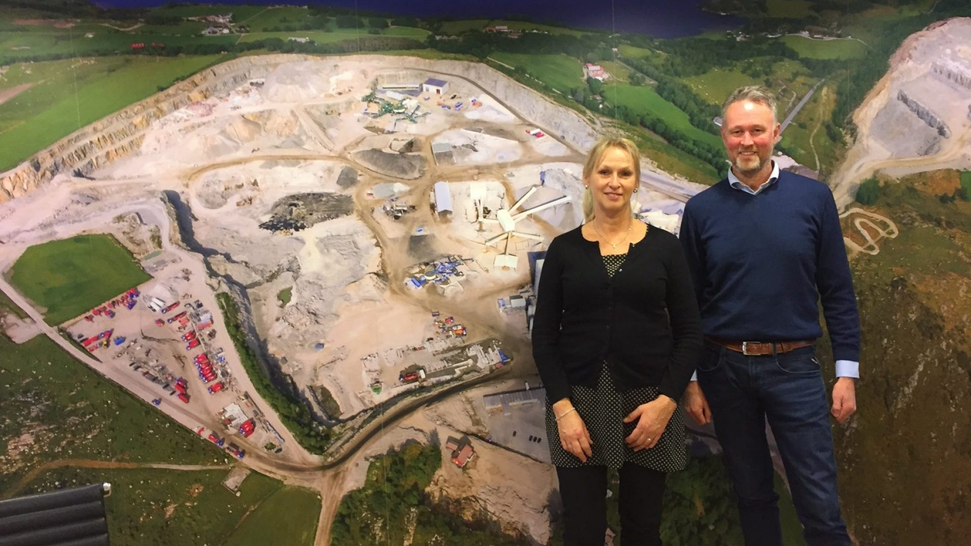 En kvinne og en mann foran et stort veggfoto.