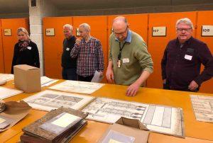 Fem menn ser på arkivmateriale