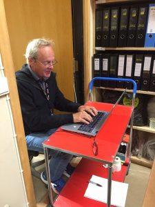 Mann sitter og skriver på PC