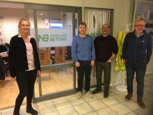 En kvinne og tre menn foran kontordør