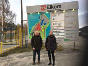 Mann og kvinne foran informasjonstavle ved fabrikk