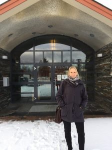 Kvinne foran inngang til bygning