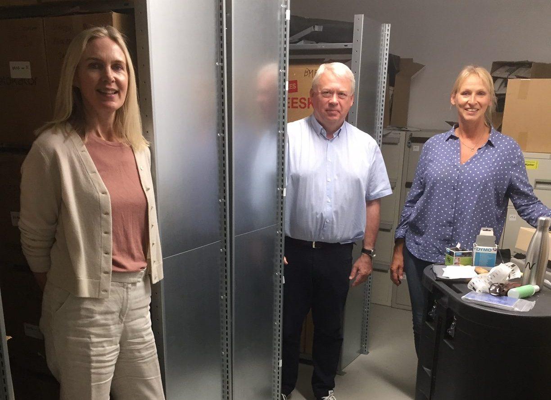 To kvinner og en mann stående i arkivmagasin