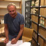 Mann noterer på papir i et arkivrom