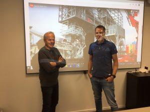 To menn foran et lysbilde fra prosjektor på kontorvegg