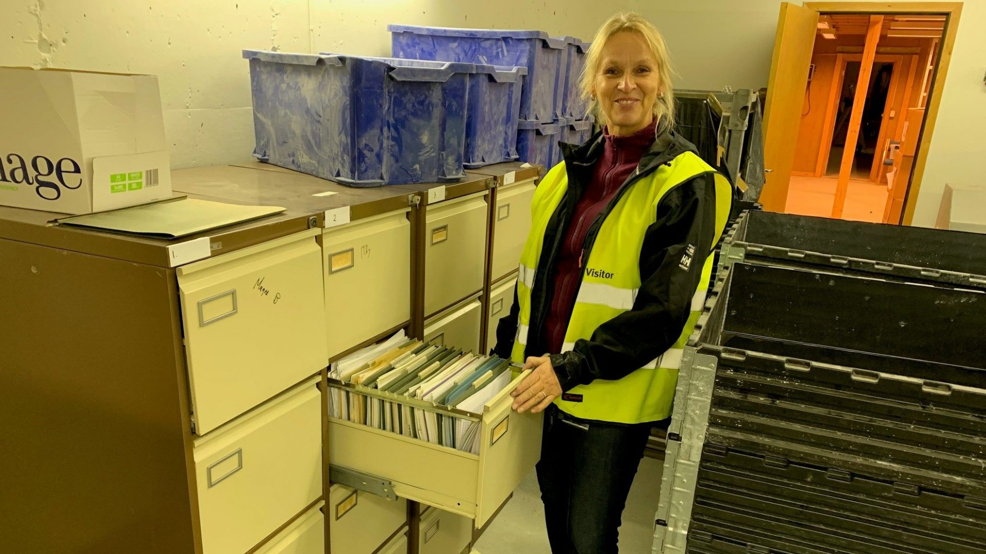 Kvinne i arkivrom foran åpne arkivskuff
